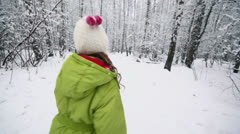 Little girl in warm clothes runs by path at winter park Stock Footage