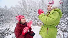 Mother with her little daughter play pat-a-cake game in winter Stock Footage
