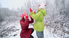 Little girl with her mother play pat-a-cake game in winter park Stock Footage