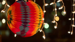 Colorful sphere circling near light lamps of garland in dark Stock Footage