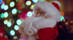 Toy Santa Claus dances and sing near Christmas tree Stock Footage