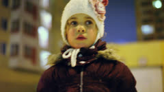 Little girl in warm clothes speaks near dwelling house at winter Stock Footage