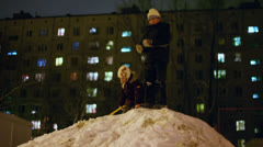 Girl goes down from snowbank where brother throws snowballs Stock Footage