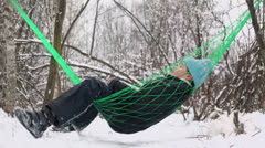 Young boy in warm clothes sways on hammock and throws snowball Stock Footage