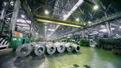Crane platform rides in warehouse with rolls of material Stock Footage