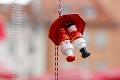 Red and White Traditional Figurines Under an Umbrella - stock photo