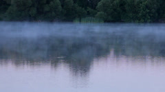 Fog moving across a lake at sunrise Stock Footage