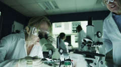 Mature male and female research experts working together in the laboratory - stock footage