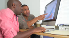 Stock Video Footage of Two African American Business men looking at data on computer