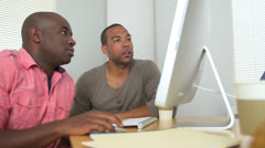 Black businessmen discussing sales data on computer Stock Footage