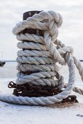 Old bollard and frozen ship cable Stock Photos