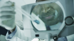 Mature male scientific researcher analyzing samples in laboratory - stock footage
