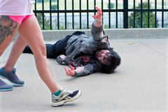 monster reaches for women passing by in atlanta zombie run - stock photo