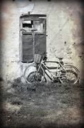 Old bicycle leaning against a ruined wall. photo in old image style. .. Stock Photos