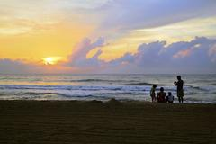 Beach silhouette of indian family and sunrise Stock Photos