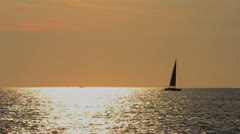 sailboat on the horizon at sunset - stock footage