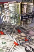 shopping trolley full dollar bill, greenback - stock photo