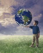 Young boy holds the world Stock Photos