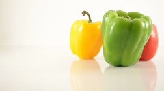 Green, Red, and Yellow Peppers On Acrylic Against White - Dolly Left Stock Footage