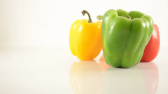 Green, Red, Orange and Yellow Peppers On Acrylic Against White - Dolly Left Stock Footage