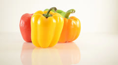 Yellow, Green, Orange and Red Peppers On Acrylic Against White - Dolly Right Stock Footage