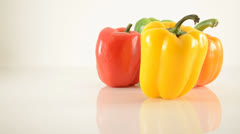 Yellow, Green, Orange and Red Peppers On Acrylic Against White - Dolly Left Stock Footage