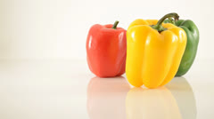Yellow, Green and Red Peppers On Acrylic Against White - Dolly Left Stock Footage