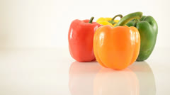 Orange, Yellow, Green and Red Peppers On Acrylic Against White - Dolly Left Stock Footage