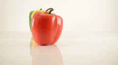 Red, Yellow and Green Peppers On Acrylic Against White - Dolly Right Stock Footage