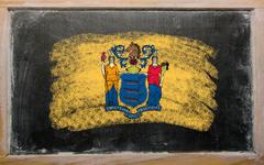 flag of us state of new jersey on blackboard painted with chalk - stock photo