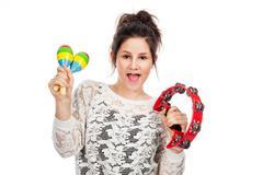 teenage girl with tambourine and maracas. - stock photo