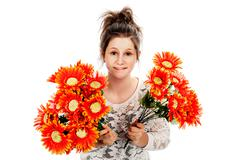 teenage girl holding two bunches of fake flowers. - stock photo