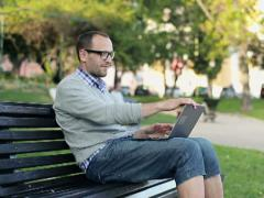 Young happy man finish work on laptop in city park NTSC Stock Footage