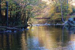 Bridge over river autumn mountains - stock photo