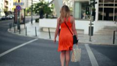 Woman with shopping bags crossing the street, steadicam shot HD Stock Footage
