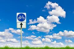 Bicycle way sign on fresh spring green grass against blue sky Stock Photos