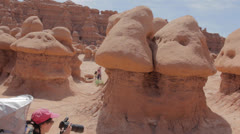A mother and baby taking pictures in goblin valley state park Stock Footage