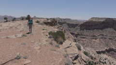 A mother and baby hiking by the edge of the grand canyon Stock Footage