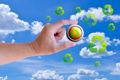 hand holding recycle button against blue sky - stock photo