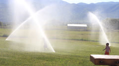 Kids Playing in the Sprinklers Stock Footage