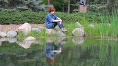 Red-haired girl on the pond Stock Footage