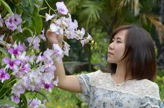 smiling woman with flower in the garden - stock photo