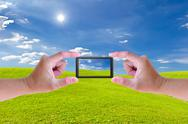 Stock Photo of hand holding mobile phone and green grass meadow