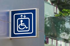Blue handicap elevator sign with blurred glass background, closeup - stock photo