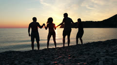 Group of people dancing on the beach at sunset, group of happy young people danc - stock footage
