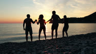 Group of people dancing on the beach at sunset, group of happy young people danc Stock Footage