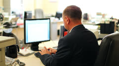 Businessman sitting at the computer in the office. View from the back. Stock Footage
