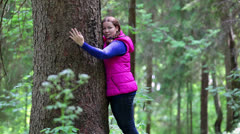 Girl hugging a big pine tree trunk in the forest Stock Footage