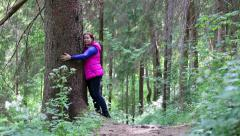 Woman walking and hugging a big pine tree trunk in the forest Stock Footage