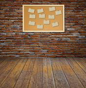 Cork bulletin board with old paper note on brick wall. Stock Photos